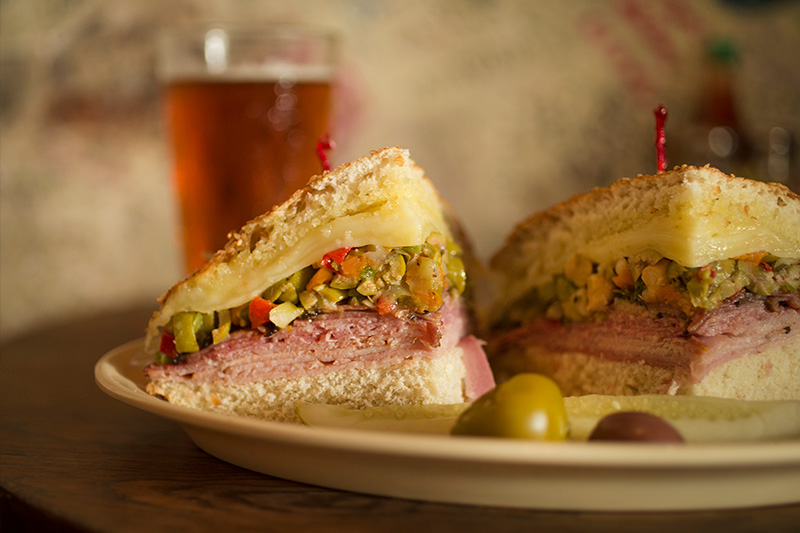 Muffuletta on plate cut into quarters